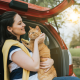 Woman holding cat in back of vehicle
